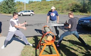 Woodland Regional High School timber team members Chris Manning, left, and Jonathan Tanguay use the cross cut saw as humanities teacher and club adviser Robert Murdy, center, looks on during practice Oct. 11 at the school in Beacon Falls. The timber team started this fall. –LUKE MARSHALL