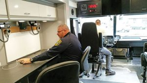 Naugatuck Police Lt. Bryan Cammarata sits at a work area as Naugatuck Det. Jay Pugliese sits at the wheel of a new DUI/support command vehicle, which will be shared with Middlebury, Watertown and Wolcott. The officers are in charge of stocking and maintaining the vehicle, as well as training people to operate it. -REPUBLICAN-AMERICAN